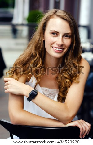 Beautiful girl with freckles and long curly hair. Lifestyle outdoor portrait - stock photo