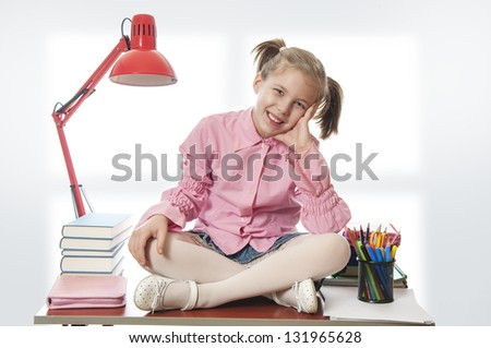 Beautiful girl with glasses sitting on a desk - stock photo