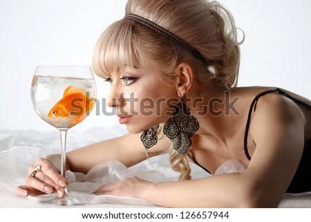 Beautiful girl with golden fish making wish - stock photo