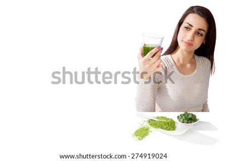 Beautiful girl with green superfood spirulina, chlorella and wheat grass isolated on white background with copy space. - stock photo