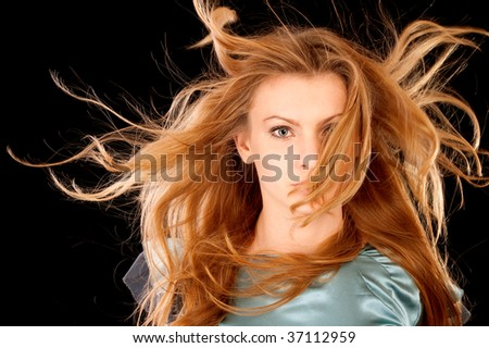 Beautiful girl with hair fluttering on wind, it is isolated on black background. - stock photo