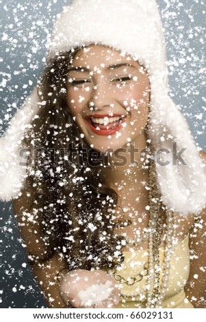 Beautiful girl with hat Blowing Snow and smiling
