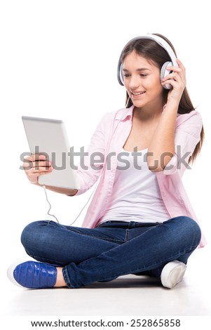 Beautiful girl with headphone and digital tablet is sitting on the floor and looking at the tablet, isolated on white background.
