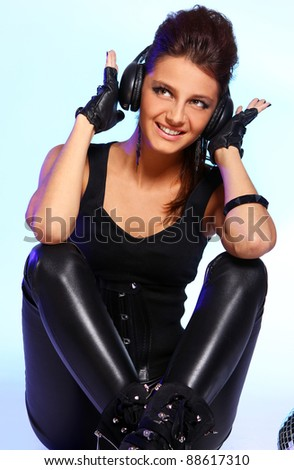 Beautiful girl with headphones and disco ball over light blue background - stock photo