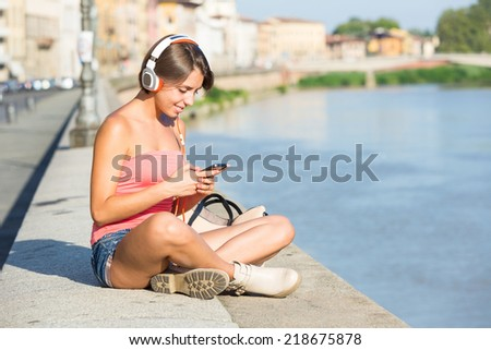 Beautiful Girl with Headphones and Mobile Phone in the City - stock photo