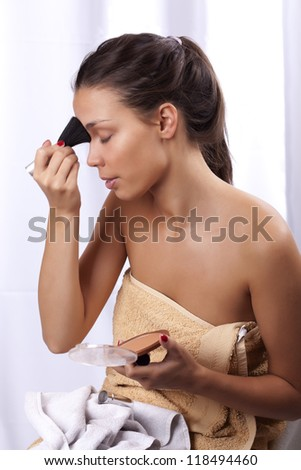 Beautiful girl with healthy skin  applying make up on her face with make-up brush