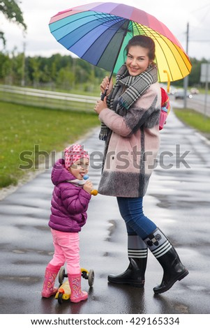 Beautiful girl with her daughter playing in the park - stock photo