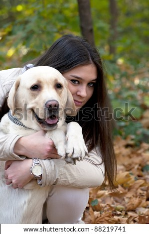 Beautiful girl with her dog in nature - stock photo