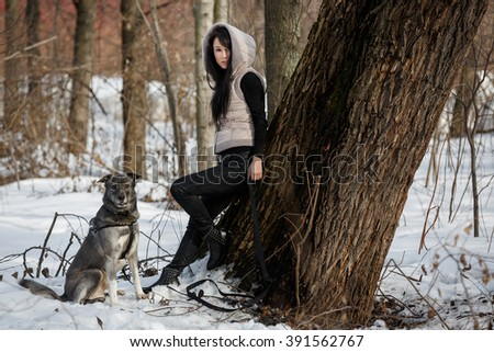 Beautiful girl with her dog in winter forest