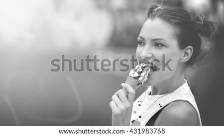 Beautiful girl with ice cream in skate park. Lens flare. Black and white