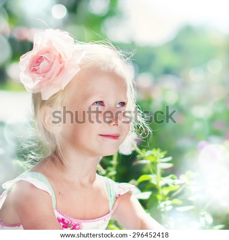 Beautiful Girl with in Pink Rose Playing in the Summer Garden, in Rays of Light - stock photo