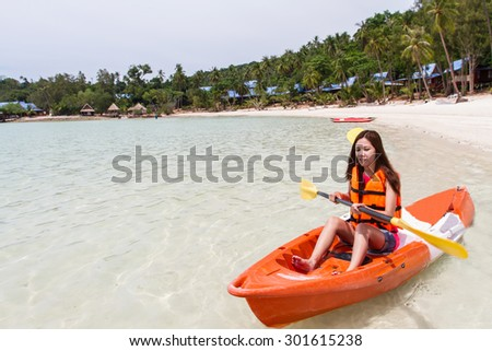 Beautiful Girl With Kayak Paddle  Travel and Vacation on The Beach enjoying - stock photo