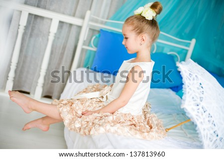 Beautiful girl with lace umbrella sitting on bed in ballerina dress and looking on her feet - stock photo
