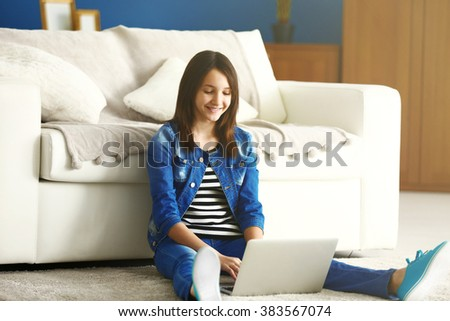 Beautiful girl with laptop on carpet indoor - stock photo