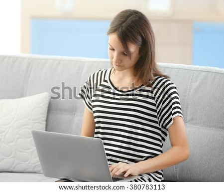 Beautiful girl with laptop on sofa indoor