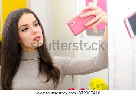 Beautiful girl with long black hair taking selfies in front of the mirror. - stock photo