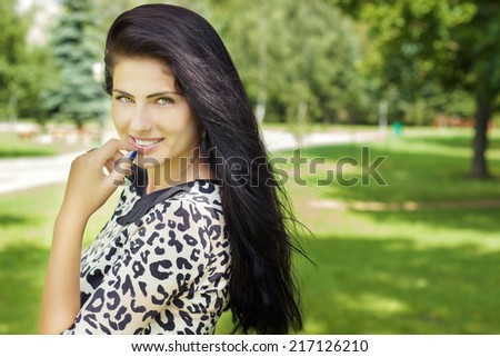 Beautiful girl with long black hair with a smile happy standing in the Park - stock photo
