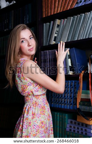 Beautiful girl with long blond hair is standing next to shelves of books and looking at camera - stock photo