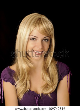 Beautiful girl with long blond hair looking at camera and smiling, black background