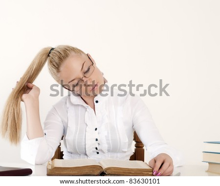 beautiful girl with long blond hair reading a book - stock photo