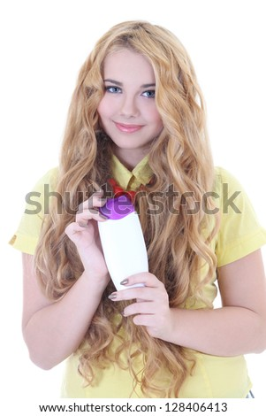 beautiful girl with long curly hair and bottle of shampoo in her hand