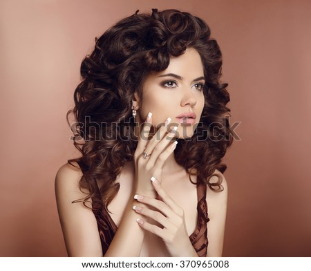 Beautiful girl with long curly hair. Makeup. Manicured nails. Brunette with healthy brown  hairstyle. Studio Photo. - stock photo