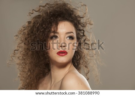beautiful girl with long curly hair on a gray background