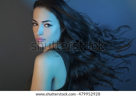 beautiful girl with long flying hair, studio blue light