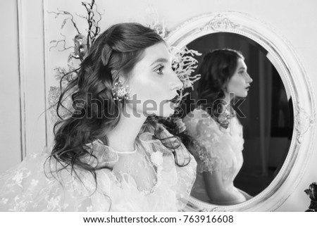 Beautiful girl with long hair and natural make-up and pale skin. A woman in a white dress. The unusual appearance. The bride in the bedroom