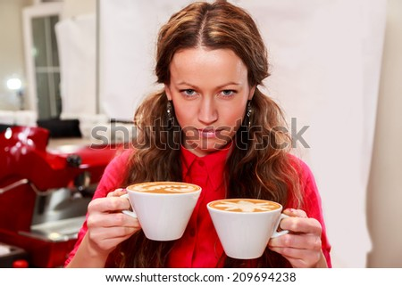 Beautiful girl with long hair in a cafe. Girl holding a cup of cappuccino, enjoying the taste and aroma. Coffee, drink, girl, catering, cup of coffe - Concept catering. Article about coffee. - stock photo
