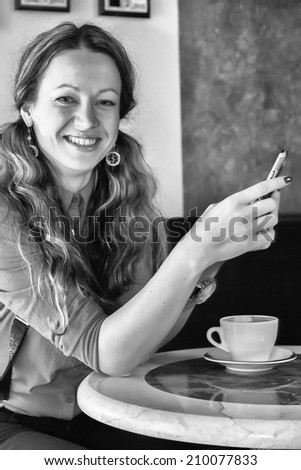 Beautiful girl with long hair in a cafe. Girl holding a cup of cappuccino, enjoying the taste and aroma. Coffee, drink, girl, catering, cup of coffe - Concept catering. Article about coffee.