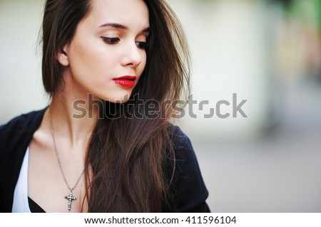 beautiful girl with long hair in a white shirt and a black cardigan looking with painted red lipstick lips - stock photo