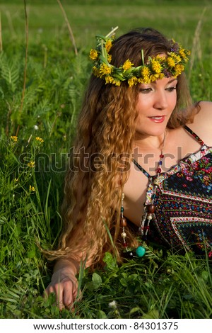 beautiful girl with long hair in wreaths of dandelions on the grass in the summer