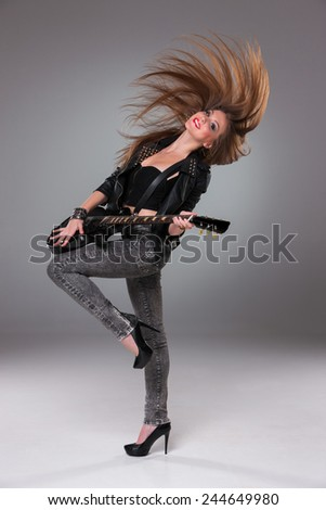 Beautiful girl  with long hair playing guitar in rock style on a gray background - stock photo