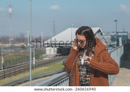Beautiful girl with long hair talking on phone in an urban context