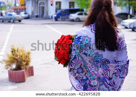 Beautiful girl with long hair with a large bouquet of roses