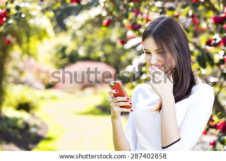 Beautiful girl with long straight dark hair reading text message on her smart phone in the garden - stock photo