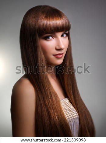 Beautiful girl with long straight hair on gray background