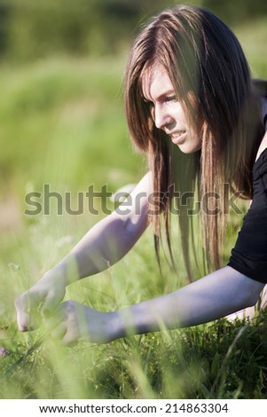 Beautiful girl with long, straight hair posing in the field