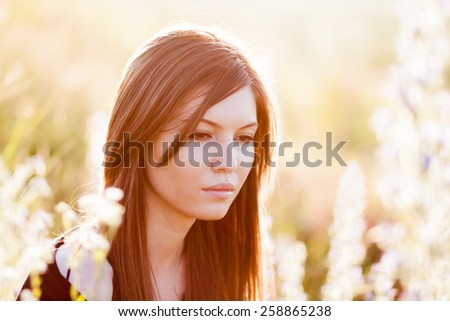 Beautiful girl with long, straight hair posing in the field looking melancholic