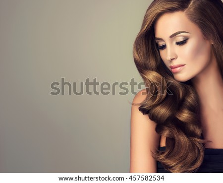 Beautiful girl with long wavy  and shiny  hair . Brunette woman  with curly hairstyle