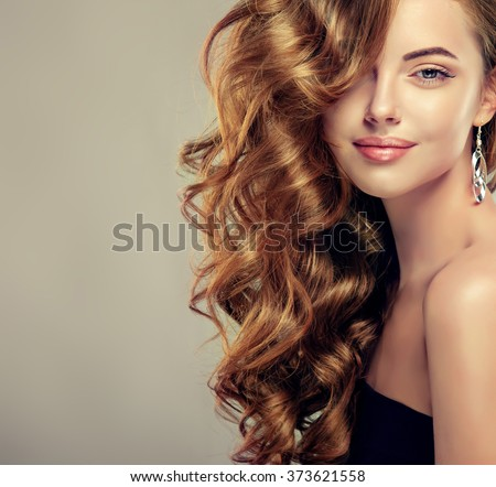 Beautiful girl with long wavy hair .  Brunette  model with curly hairstyle - stock photo