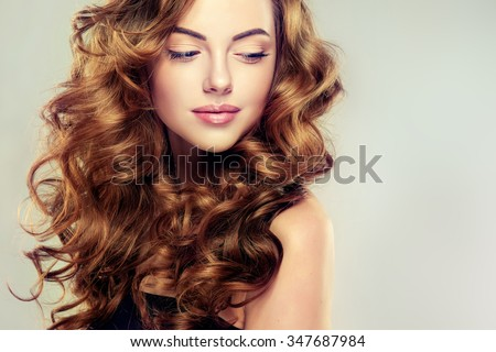 Beautiful girl with long wavy hair .  Brunette with curly hairstyle - stock photo