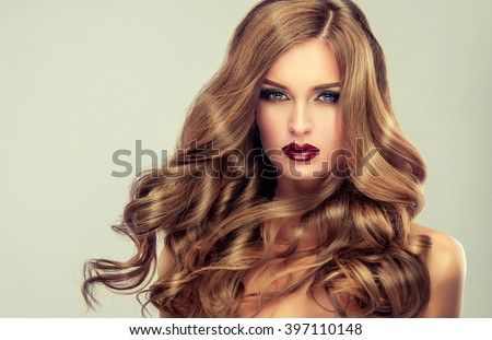 Beautiful girl with long wavy hair .  fair-haired  model  with curly hairstyle   and fashionable makeup . Bright purple lips - stock photo
