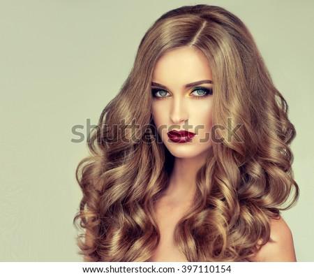 cô gái xinh đẹp với mái tóc lượn sóng dài.  tóc vàng mô hình với kiểu tóc xoăn và trang điểm thời trang.  môi tím Bright