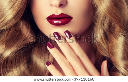 Beautiful girl with long wavy hair .  woman with red manicure .  girl with plum color nail Polish on the nails . Makeup and cosmetics - stock photo