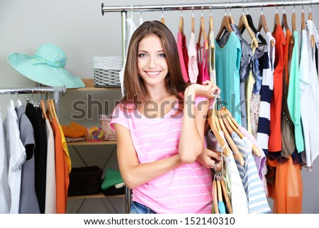 Beautiful girl with lots  clothes in room background