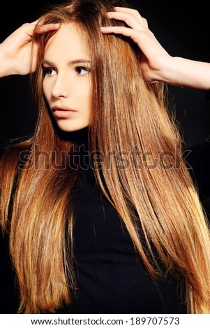 Beautiful girl with magnificent long hair posing over black background.