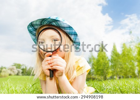 Beautiful girl with magnifier laying on the grass - stock photo
