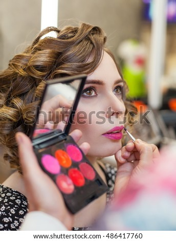 Beautiful girl with make-up and hairstyle. Stylist making make-up woman. Portrait of a young woman on a morning.